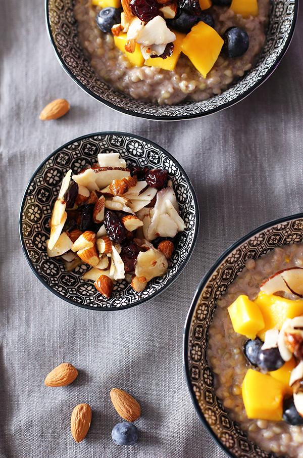 Rezept Frühstück Buchweizen-Porridge mit Mango und Blaubeeren und karamellisierten Mandeln,  Cranberries und Kokoschips